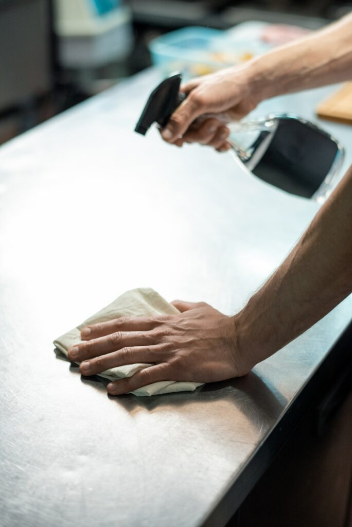 Hands of contemporary chef of restaurant spraying sanitizer on kitchen table