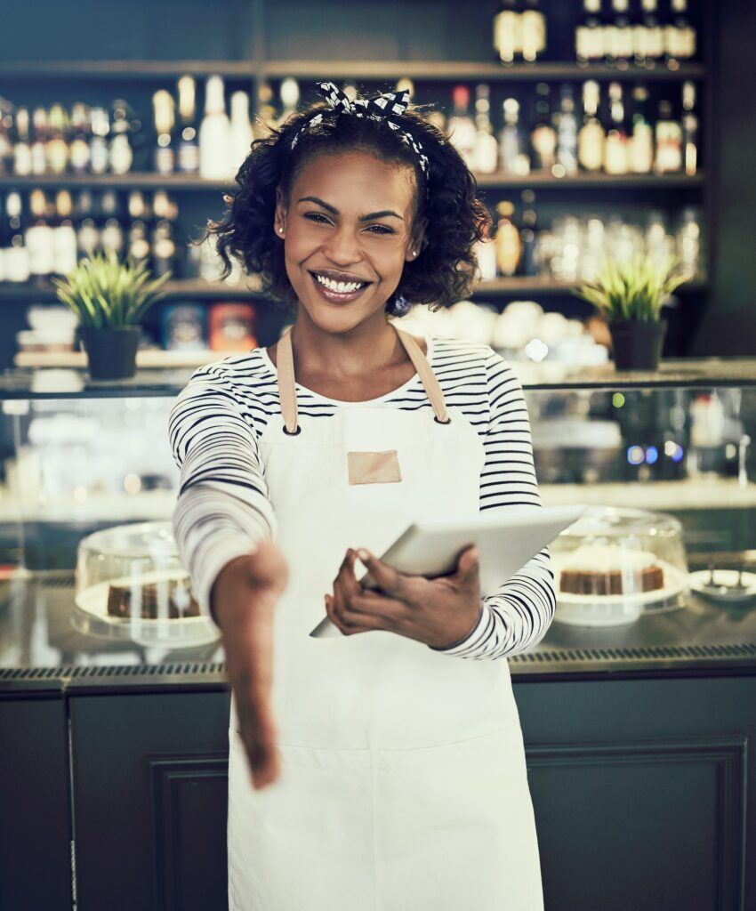 Smiling hostess offering a handshake in a cafe